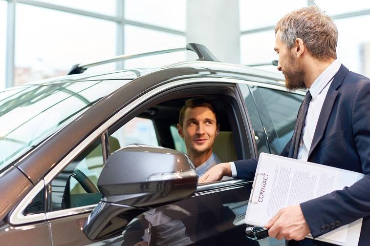 남자 손님이 자동차 구매를 위해 자동차에 시승하고 있는 모습