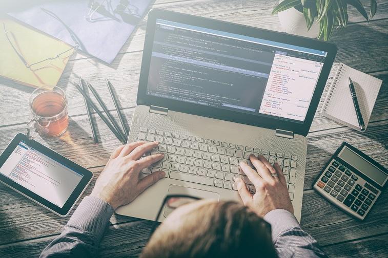 코딩작업중인 남자와 노트북, 태블릿이 놓인 책상
