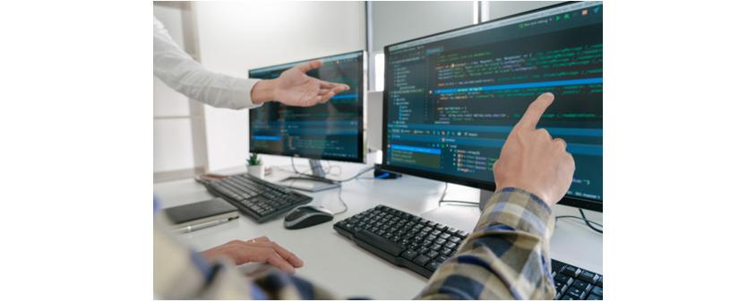 두 대의 모니터로 코드를 리뷰하며 협의하는 장면