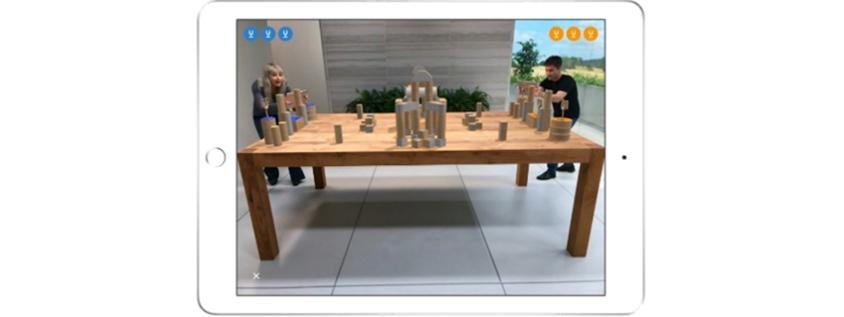 테이블을 사이에 놓고 남녀가 양쪽에서 ARKit이 탑재된 아이패드로 증강현실 게임을 즐기는 모습
