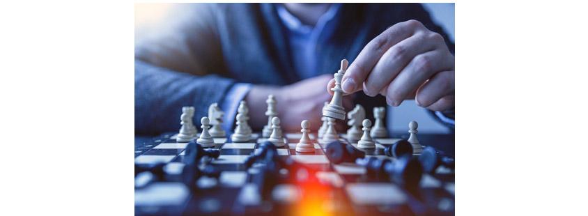 누군가 체스를 두고있는 장면, 체스판에 체스말을 손에쥐고 있음